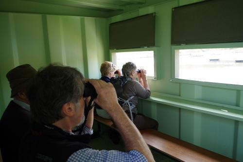 Members using binoculars in a bird hide
